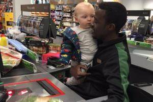 Kind-hearted cashier entertains baby so mum can get shopping done